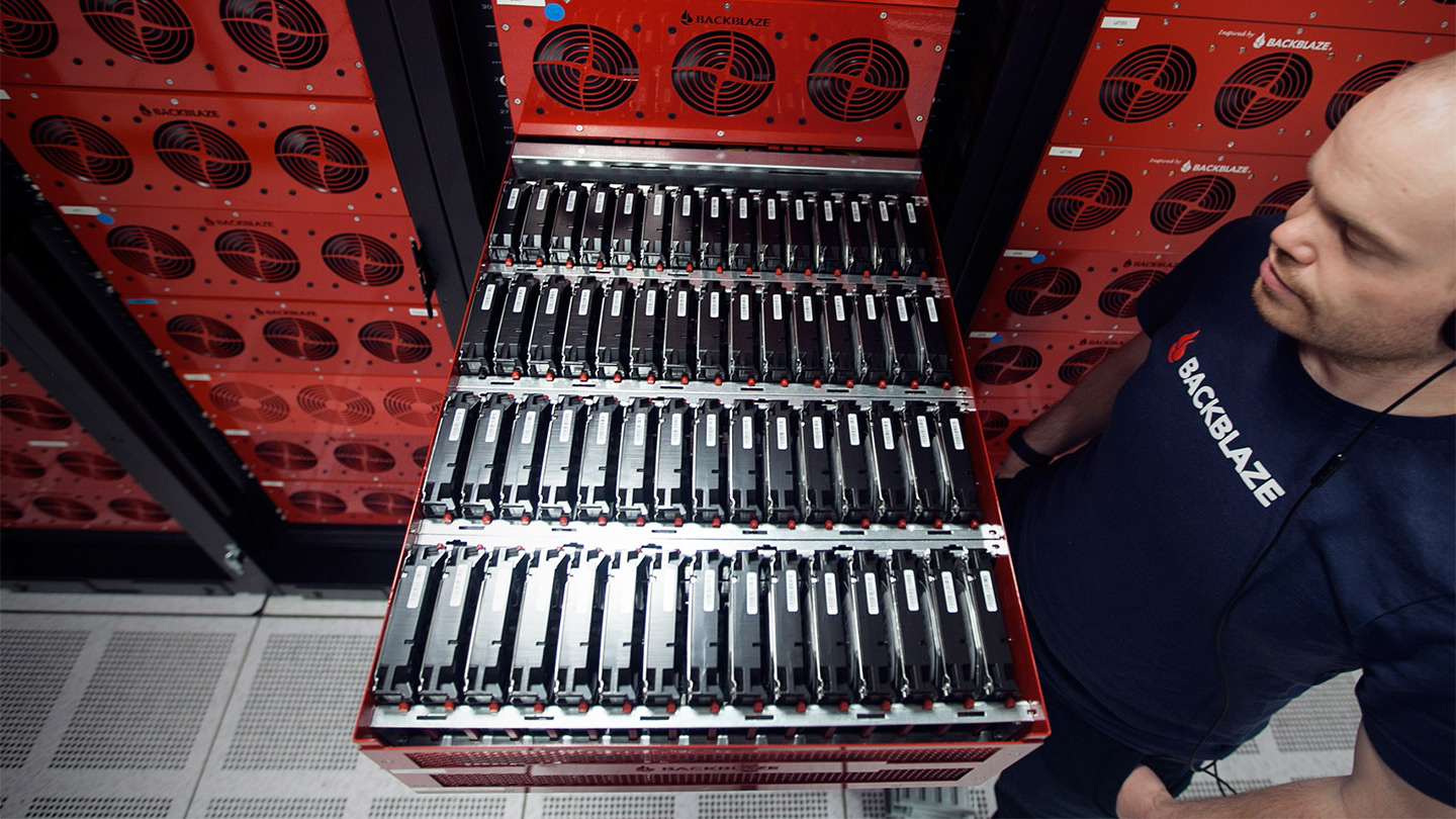 a tech standing looking at a pod full of hard drives in a data center
