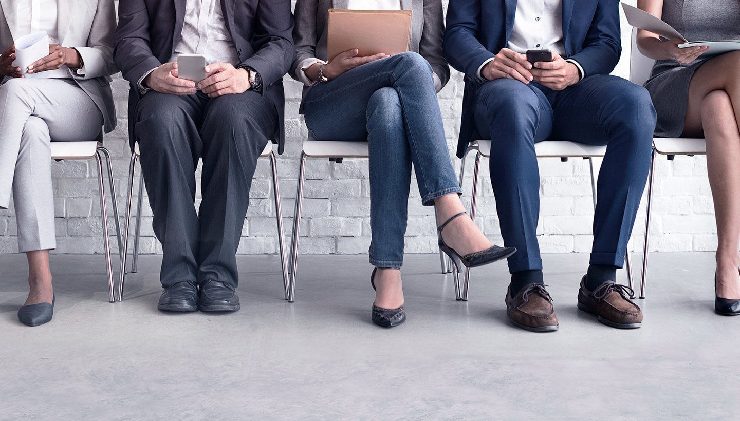 row of potential employee hires sitting waiting for an interview