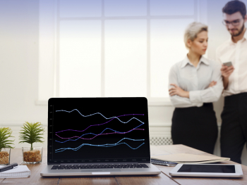 computer with line chart on a desk with a man and woman standing near it